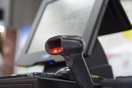a hand held barcode scanner, scanning barcode ; shine red light;destop background Banque d'images