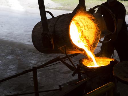 용철 탕을 국자에 붓는다. 파운드리 공장 스톡 콘텐츠