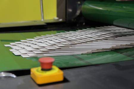 carton boxes on conveyor belt of a flolder gluer machine