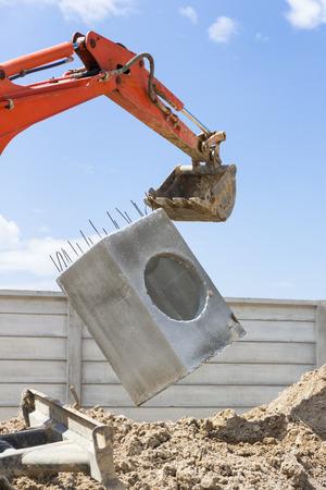 Excavator lift a manhole at construction site Stock Photo