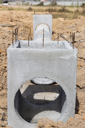 Precast concrete manholes are stored on the ground ready for construction; for draining storm water.  Stock Photo