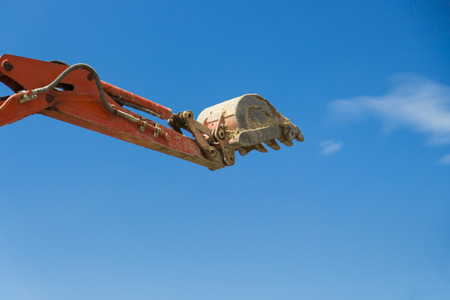 cargador frontal: Excavator working at construction site against blue sky