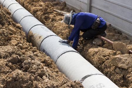 Arbeider installeert Prefab betonnen mangaten; voor het afvoeren van regenwater.