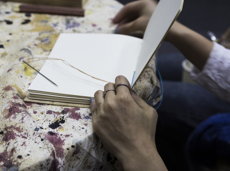 women worker binding pages in for handmade book