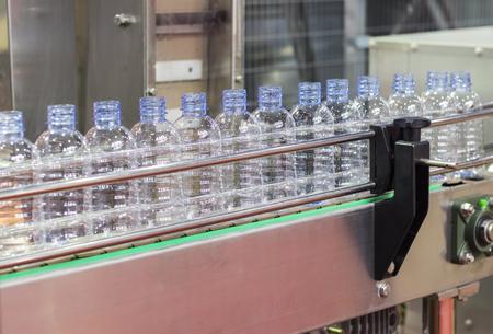 Botella de agua PET en el transportador de la máquina etiquetadora
