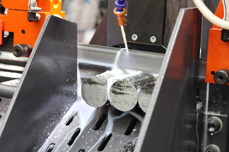 Steel bar cutting by band saw machine with coolant 스톡 콘텐츠