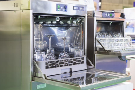 Open dishwasher with clean glass, cups, plates and dishes, selective focus Banco de Imagens