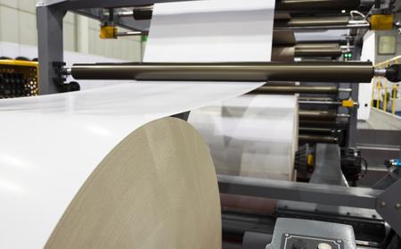 Rolle weißes Papier in moderner Papierschneidemaschine