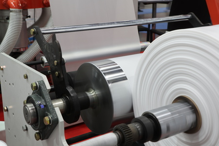 Winding unit of extrusion plastic film blowing machine ; close up Stock Photo