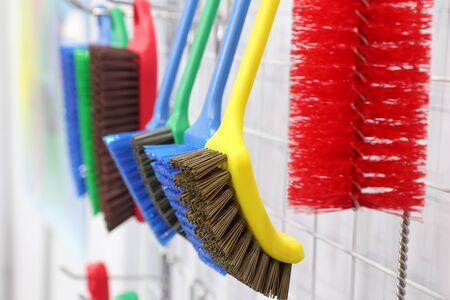 plastic cleaning brushes in supermarket hanger ; close up Stock Photo