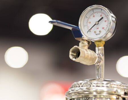 Pressure dial Gauge for measuring air pressure in manufacturing equipment ; industrial background