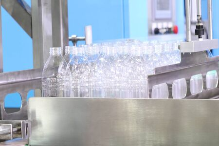 a group of platic bottles in production line wait to fill water . engineering equipment indutrial background