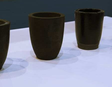 the small black ceramic crucible for transfer molten metal into mold ; industrial engineering equipment background