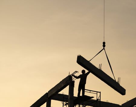 precast concrete beam installed at construction site by mobile crane and worker  ; silhouette picture ; civil engineering background