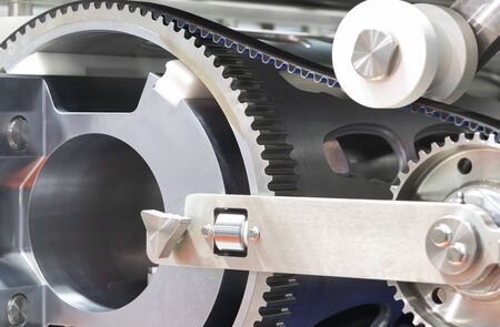 Black timing belt that synchronizes the rotation of gear drum in NUGGETS MEAT FORMING AUTOMATIC machine ; industrial engineering background