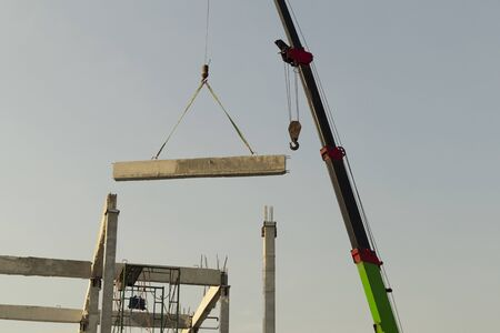 precast concrete beam installed at construction site by mobile crane ; civil engineering background