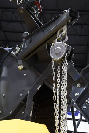 Hoist with chain in swing arm of machinery Banque d'images