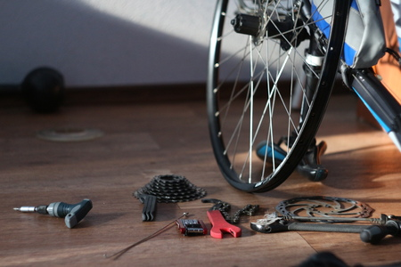 tools scattered on the floor next to a disassembled bicycle