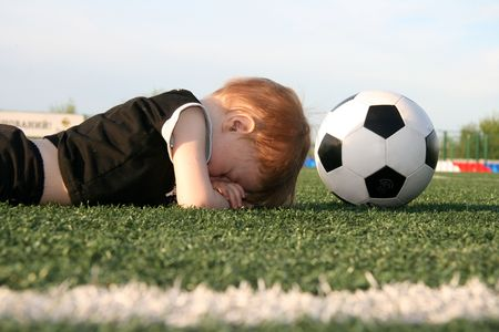 weariness: Figure of the boy and football on an artificial covering of stadium