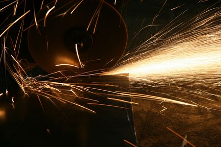Working of metal at a factory. A loop of sparks at cutting a detail
