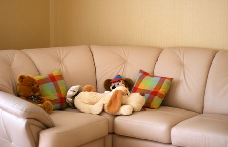 Group of soft toys on a light leather sofa