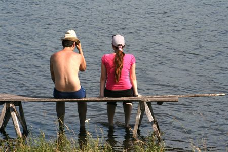 On coast of lake the guy and the girl sit