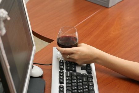 Female hand with a wine glass fault on the keyboard of a computer Stock Photo