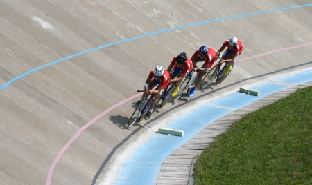 Team of bicyclists on a bicycle track during competitions Stock Photo