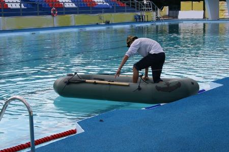 Der junge Mann sitzt in ein Boot zu cross-pool