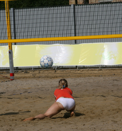 The girl beats off a ball. Beach volleyball photo