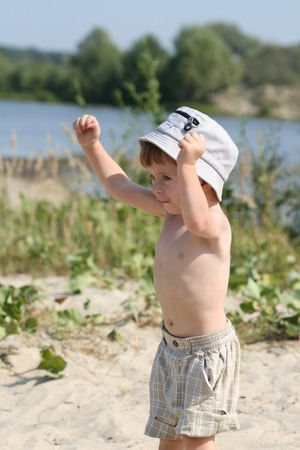lifted hands: The emotional boy on a beach with the lifted hands Stock Photo
