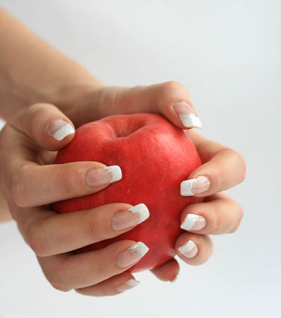 Female fingers with manicure hold an apple Stock Photo