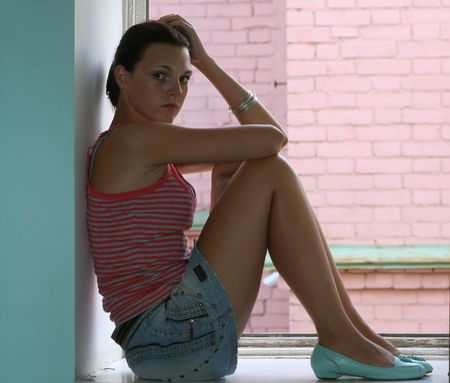 The thoughtful girl in a short jeans skirt
