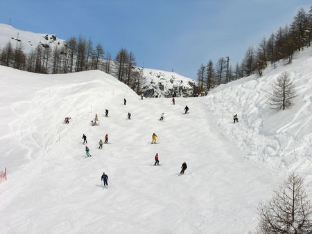 The big group of skiers on a mountain slope Stock Photo