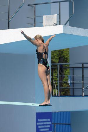 springplank: Het meisje bereidt voor een sprong in het water