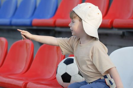observes: The young fan on a tribune of stadium observes of game in football