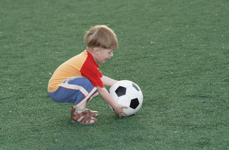 establishes: The kid establishes a ball on a football field Stock Photo