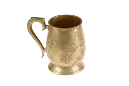 Ancient bronze mug with a flower ornament Stock Photo