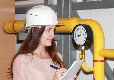 The girl the operator writes down indications of pressure of gas