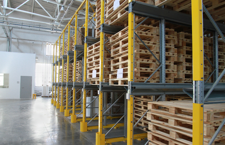 Wooden pallets on racks of the big warehouse