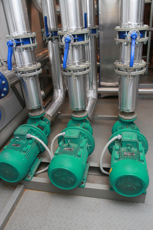 Three industrial pumps established on a floor in a boiler-house