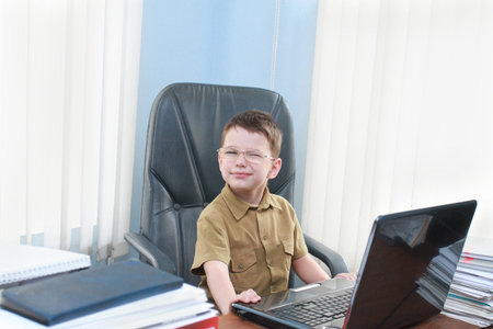The little boy on a workplace at office with the laptop