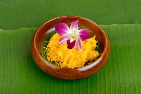 Kanom Foythong (thai name), Thai dessert on banana leaf green background. photo