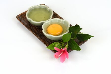 Egg yolks and egg whites in a cup have medicinal properties and placed on a white background.