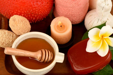 Face mask and soap with gac fruit extract and honey, spa treatment concept, medicinal properties on a white background.