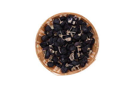 Dried black wolfberry in bamboo basket isolated on white