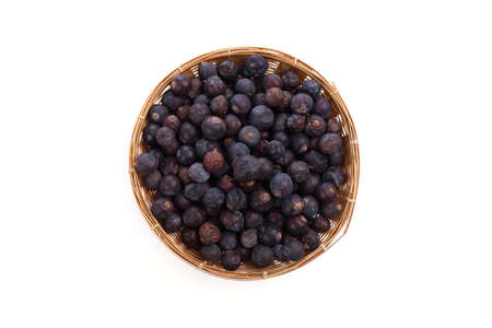 Dried Juniper Berry in a bamboo basket isolated on white