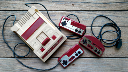 BANGKOK, THAILAND - MARCH 31, 2017 : Old Nintendo Entertainment System Family Computer and Hori Controller on wooden background.
