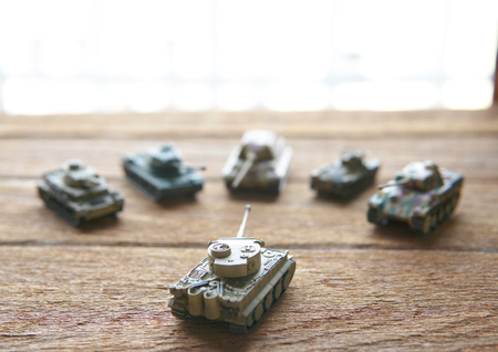 old toy tanks on wooden background.The battle.