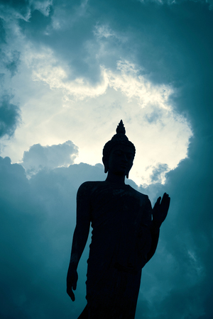 silhouette buddha statue on blue sky background